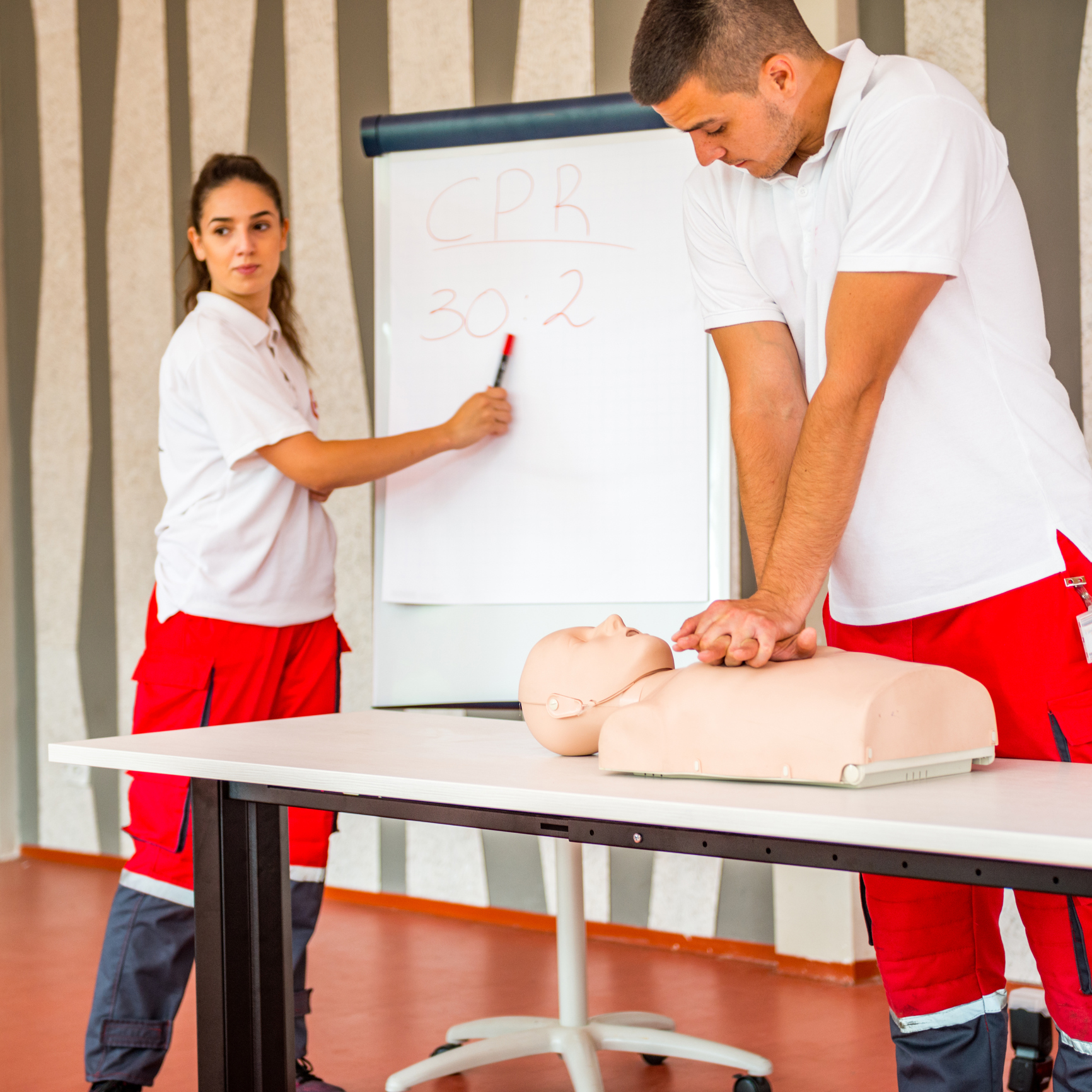 CPR class with instructors talking and demonstrating first aid technique on a CPR dummy